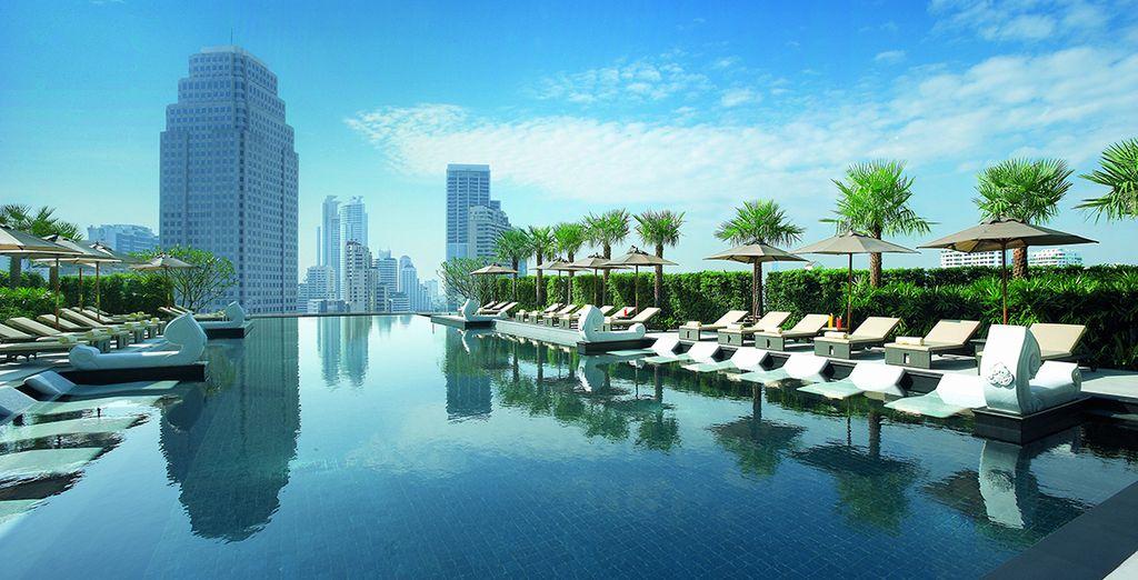 Hôtel de luxe avec piscine extérieure et espace détente offrant une vue panoramique sur la ville de Bangkok