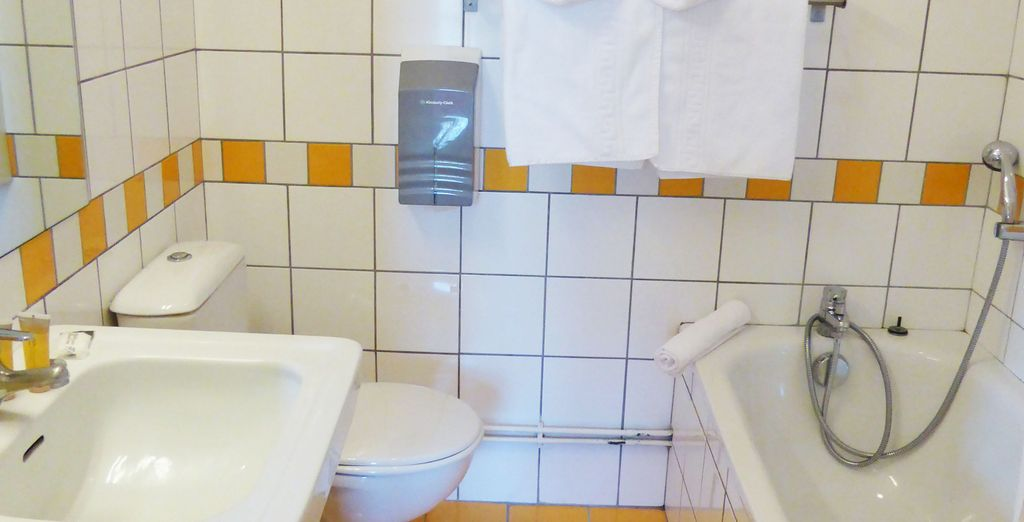 Avec une salle de bain lumineuse et fonctionnelle