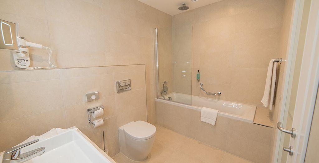 Avec une salle de bain lumineuse et spacieuse