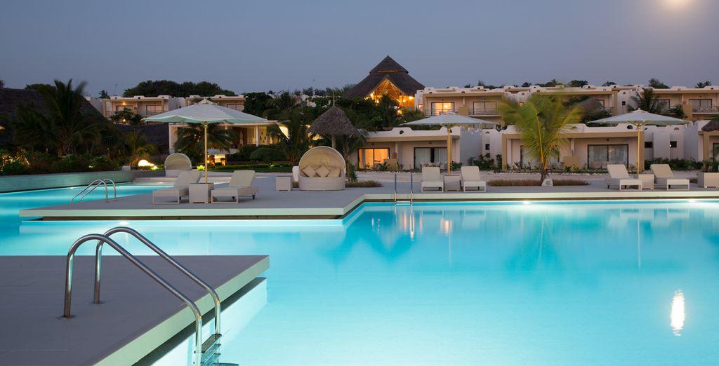 Ammirate la splendida piscina circondata da palme e ombrelloni