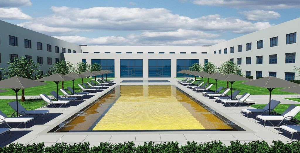 Dip into the expansive pool lined with sun loungers