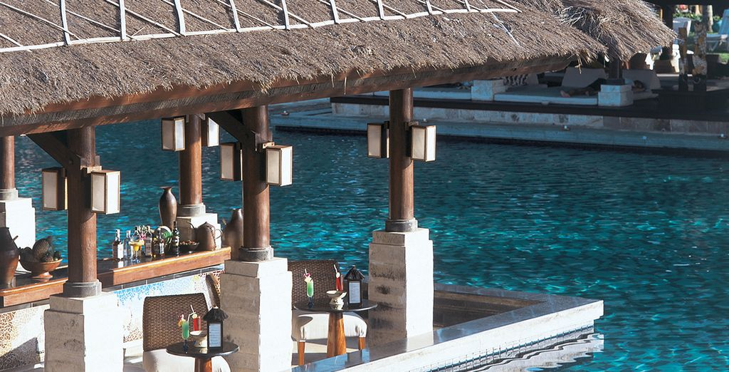 Return in the afternoon to cool off and relax by the pool's swim-up bar